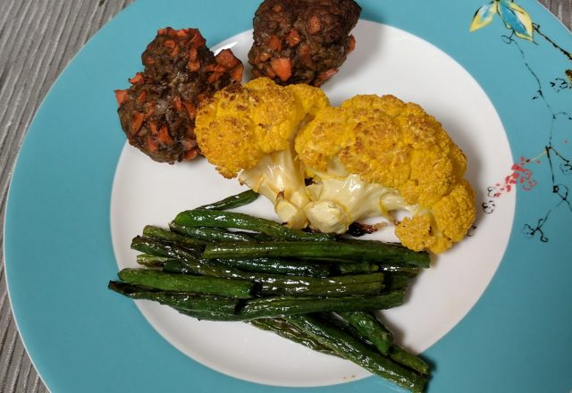 Plate of three meatballs with carrot in them, cauliflower and green beans